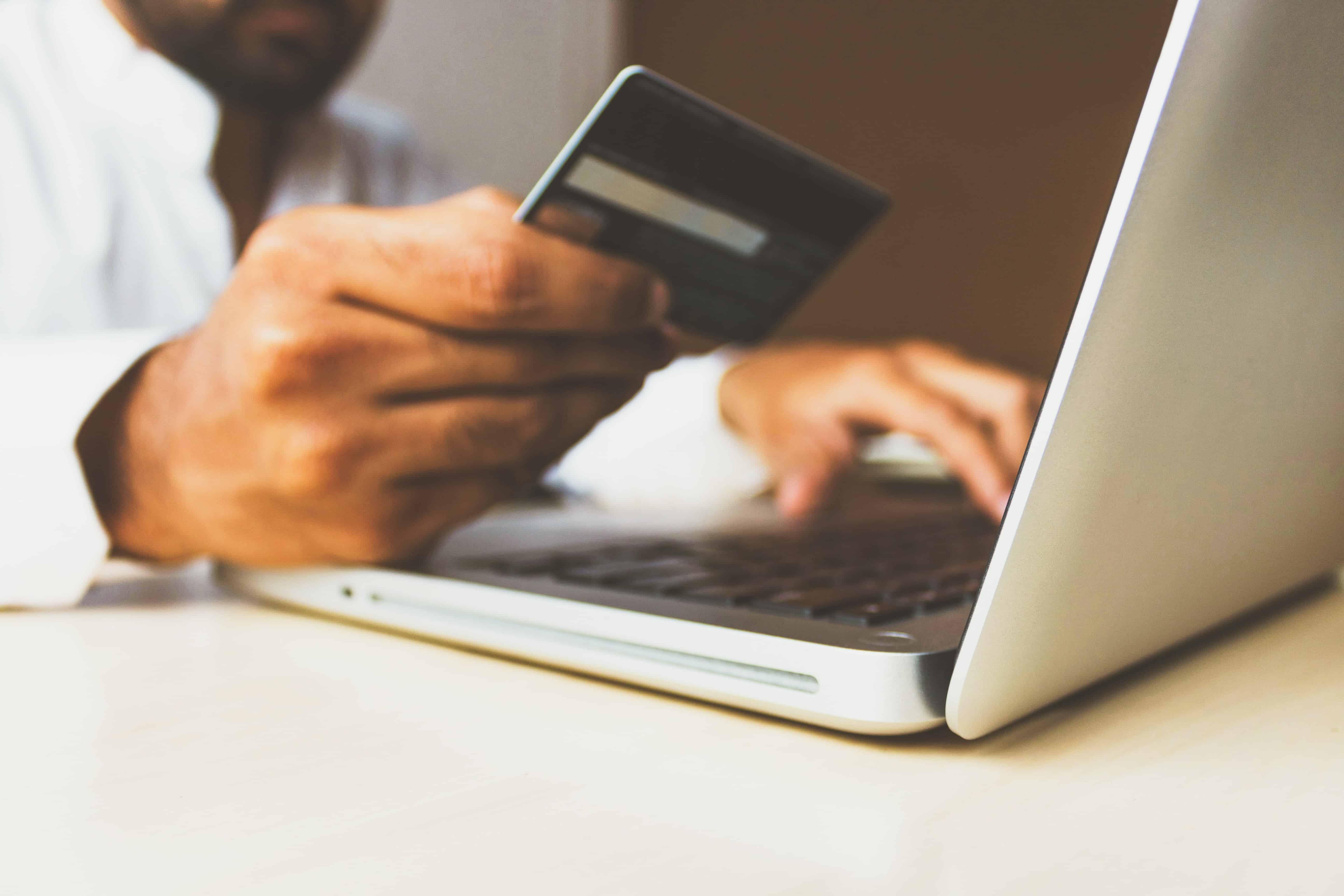 Zoom em mão masculina segurando um cartão de crédito enquanto utiliza um laptop